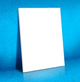 Blank white Canvas poster leaning at blue cement room, Mock up Stock Image
