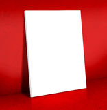 Blank white Canvas poster leaning at red cement room, Mock up Royalty Free Stock Photo