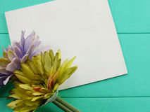 Blank white card and artificial gerbera flower valentines day on green background Royalty Free Stock Images