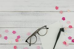 Blank white card, eyeglasses and oblique pen. Decorate with pink paper flowers on white wood background with copy space Royalty Free Stock Images
