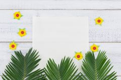 Blank white card with fern leaves and yellow paper flowers. On white wood background with copy space Stock Images
