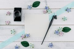 Blank white card, oblique pen and bottle of ink. Decorate with blue tone paper flowers and ribbon on white wood background with copy space Royalty Free Stock Photos