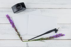 Blank white card, oblique pen and bottle of ink. Decorated with violet liatris flowers on white wood background Royalty Free Stock Images