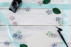 Blank white card, oblique pen and bottle of ink. Decorate with blue tone paper flowers and ribbon on white wood background with copy space Stock Photo
