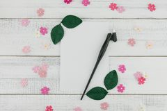 Blank white card and oblique pen decorate with pink paper flowers. And green leaves on white wood background Royalty Free Stock Photos