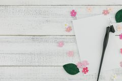 Blank white card and oblique pen decorate with pink paper flowers. And green leaves on white wood background with copy space Royalty Free Stock Photo