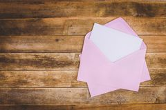 White card and pink envelope. Blank white card in pink envelope on old wooden table, top view royalty free stock photography