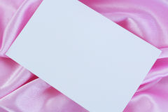 Blank white card on pink satin Royalty Free Stock Photos