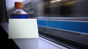 Blank white card put on the bottle near by windows shield with blurred background of transportation Stock Image
