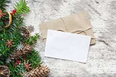 Blank white christmas greeting card and envelope with fir tree branches, food decorations and pine cones Stock Photography