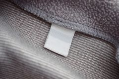 Blank white clothing label on gray fabric texture background. Close up stock photos