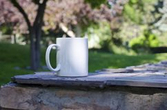 A blank white coffee mug under the pink trees stock photo