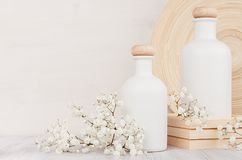 Blank white cosmetics bottles with small flowers on white wood board, copy space. Interior.