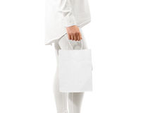 Blank white craft paper bag mockup holding hand, clipping path. Royalty Free Stock Images