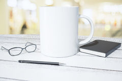 Blank white cup with diary, pen and eyeglasses on white wooden t Royalty Free Stock Photos