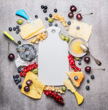 Blank white cutting board and various cheese with knife ,berries and honey Royalty Free Stock Images