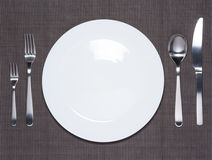 Blank white dish, fork, spoon and knife Stock Photography