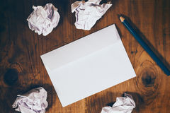 Blank white envelope, pencil and crumpled paper on wooden desk Stock Photo