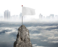 Blank white flag on mountain peak with cloudy sky cityscape Royalty Free Stock Images