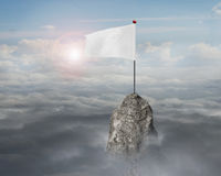 Blank white flag on mountain peak with sky cloudscape sunlight Royalty Free Stock Images