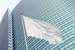 Blank white flag on pole waving in the wind against modern office building royalty free stock image