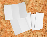Blank white folding paper flyer. Identity design, corporate templates, company style, set of booklets, blank white folding paper flyer on a cork background Stock Images