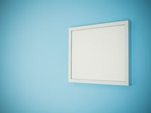 Blank white frame on light blue wall background Royalty Free Stock Image
