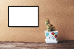 Blank white frame mockup with cactus in ceramic pot on wooden ta. Ble on vintage tone. Poster product design styled mock-up Stock Photo