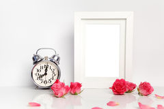 Blank white frame, pink roses and alarm clock. Mock up. Royalty Free Stock Photography