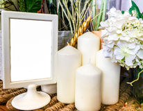 Blank White Frame on Wooden Table with Candle and Flowers used as Template Stock Photo