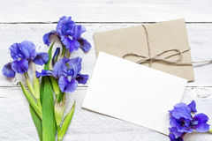 Blank white greeting card with blue iris flowers bouquet and envelope Stock Photos