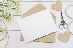 Blank white greeting card with brown envelop. And daisy flowers on wooden table with vintage tone Stock Images