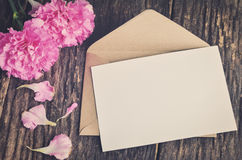 Blank white greeting card with brown envelope. And pink carnation flower on wooden table with vintage and vignette tone stock images