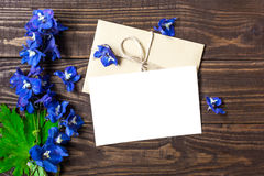 Blank white greeting card and envelope with blue wildflowers. On brown rustic wood background for creative work design royalty free stock photo