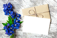 Blank white greeting card and envelope with blue wildflowers. holiday background Stock Image