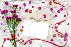 Blank white greeting card and envelope with flowers and red ribbon. Blank white greeting card and envelope with purple carnation flowers and red ribbon with stock images