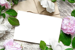 Blank white greeting card and envelope in frame of roses flowers. Over white wooden background. mock up. top view. wedding invitation Stock Image