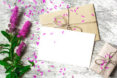 Blank white greeting card and envelope with purple wildflowers and vintage gift box. On white rustic wood background with petals around for creative work design stock photos