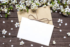 Blank white greeting card and envelope with spring blossoming ch. Erry branch on rustic wooden background. mock up. top view Stock Photography