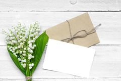 Blank white greeting card and envelope with spring lily of the valley flowers. Valentines or womens day background. top view. mock up stock photo