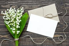 Blank white greeting card and envelope with white lily of the valley flowers Stock Images