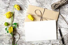 Blank white greeting card and envelope with yellow autumn flowers and pencil Stock Photos