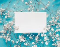 Blank white greeting card on little white flowers at turquoise blue background stock photography