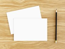 Blank white greeting card mockup with pencil on wooden table, 3D rendering. Blank white greeting card mockup with pencil on wooden table, top view, 3D rendering Royalty Free Stock Image