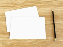 Blank white greeting card mockup with pencil on wooden table, 3D rendering. Blank white greeting card mockup with pencil on wooden table, angled top view, 3D Stock Photo