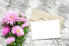 Blank white greeting card with pink aster flowers bouquet and envelope. On white wooden background. top view. mock up Stock Image