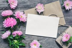 Blank white greeting card with pink aster flowers, buds and gift box over rustic wooden background. flat lay. mock up Stock Photos