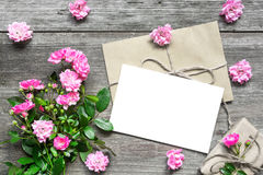 Blank white greeting card with pink rose flowers bouquet and envelope with flower buds and gift box. On rustic wooden background. top view. mock up royalty free stock photo
