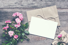 Blank white greeting card with pink rose flowers bouquet and envelope with gift box. On rustic wooden background. vintage toning .top view. mock up stock images