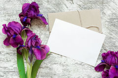 Blank white greeting card with purple iris flowers bouquet and envelope Royalty Free Stock Photo